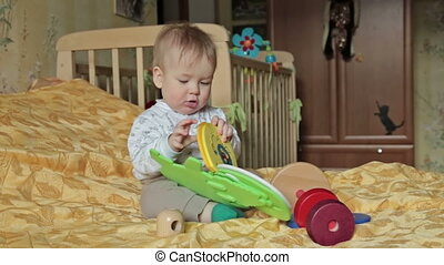 Happy baby boy playing with toy, sitting on the bed