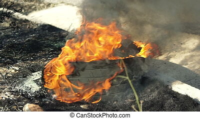 Tire Burning on Side of Road Static - Burning tire on the...