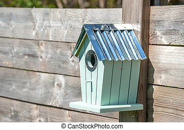 Cute birdhouse hanging on a fence
