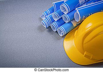 Building helmet blue rolled engineering drawings on grey...
