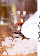 spa products (towel, salt, candles) on wooden background