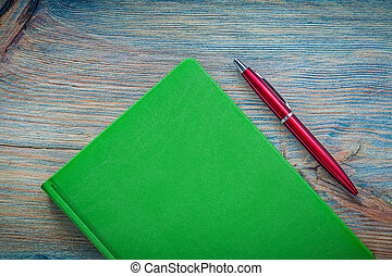 Notepad ball-point pen on wooden board top view education concep