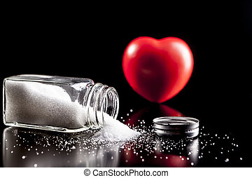 Heart Of Salt - Heart and salt isolated on black background...