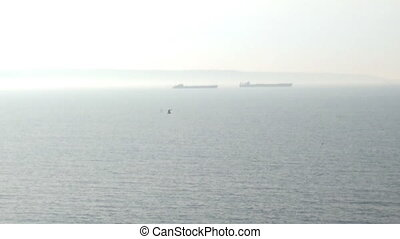Ships are in Strait of sea, foggy day