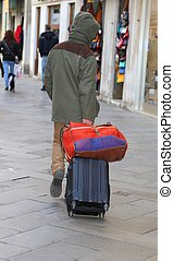 Vagabond with suitcase luggage trolley in Venice in Italy -...