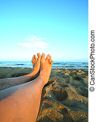 two bare feet and long legs of man on the sandy beach at...