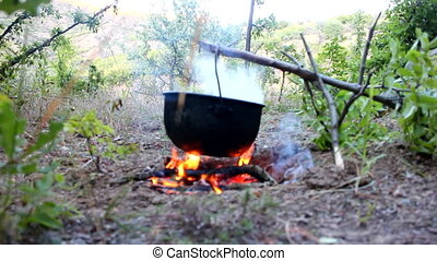 Camp life On fire to boil pot of soup for traveler - Lunch...
