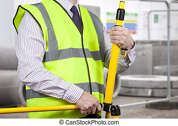 Building surveyor in high visibility setting up tripod -...