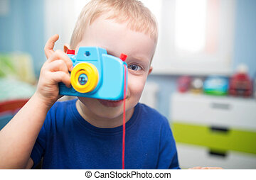 Snap - A photo of small boy playing with toy camera and...
