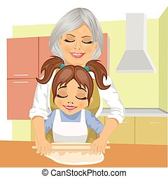 grandmother teaching granddaughter how to roll out dough to cook a pizza in kitchen