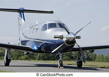 Single turboprop aircraft parked on runway. - Single...