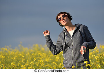 Pretty young woman listening music in earphones in the...