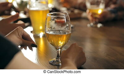 A fun company is drinking beer at the bar - A bar table with...