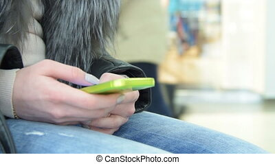 Girl using smartphone in trade centre - Close-up shot of a...