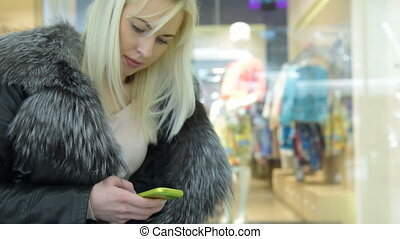 Girl using mobile in trade centre - Blond girl with...