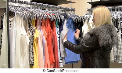 Young woman choosing clothes in the store - Blond girl...