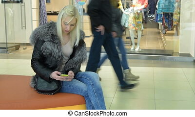 Girl communicating with mobile messaging in the shopping...