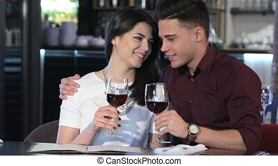 Man hugs his girlfriend at the restaurant - Handsome...