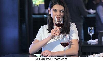Girl drinks wine at the restaurant - Pretty brunette girl...