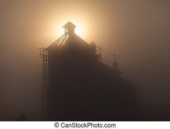 silhouette of a church steeple at sunset.