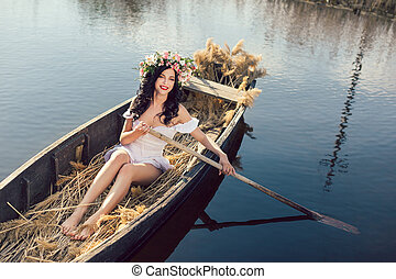 Fantasy art photo of a beautiful girl sitting in boat -...