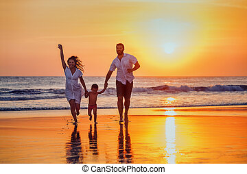 Father, mother, baby have a fun on sunset beach - Happy...