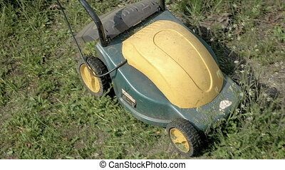 Mowing grass in the garden with electrical machine - Mowing...