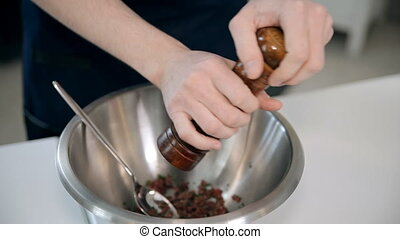 A chef is adding salt and pepper - Male hands are adding a...