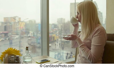 Girl drinking tea in cafe and looking out the window - Blond...