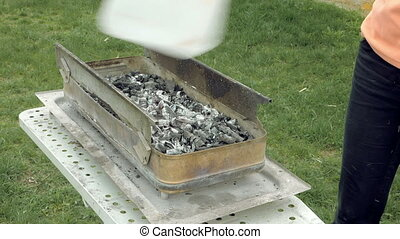 Girl blows coals and embers in a barbecue brazier - Girl...