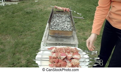 Girl puts barbecue skewers with meat on brazier - Girl puts...