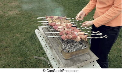 Girl cooks barbeque skewers with meat on brazier - Girl...