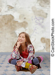 young teenager sitting cross-legged on the floor