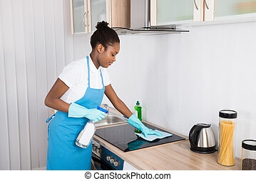 Female Janitor Cleaning Induction Stove - Young Happy Female...
