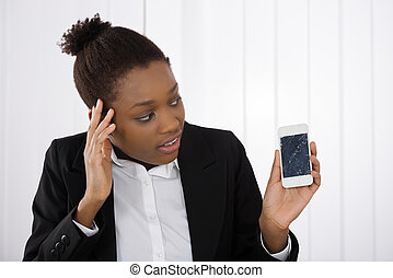 Worried Businesswoman Holding Smartphone With Cracked Screen...