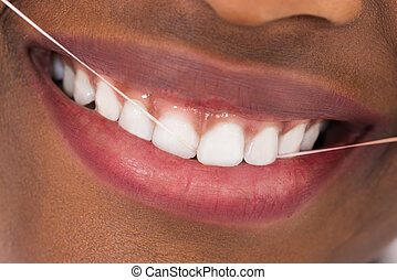 African Woman Flossing Teeth - Close-up Of Young African...