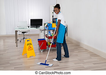 Female Janitor Mopping Floor In Office