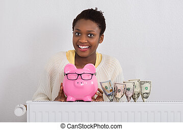 Smiling African Woman With Piggy Bank
