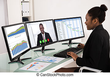 Businesswoman Working With Multiple Computer - Young African...