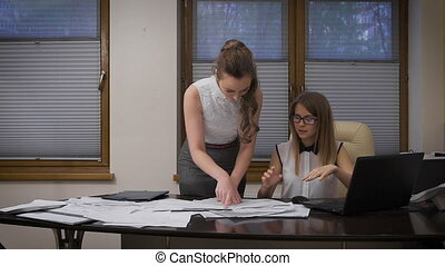Two young business women working on a serious project. They...