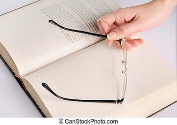 Woman hand with glasses on book isolated