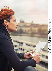 Female tourist looking at city guide - Female tourist...