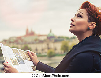 Female tourist looking at city guide - Young female tourist...