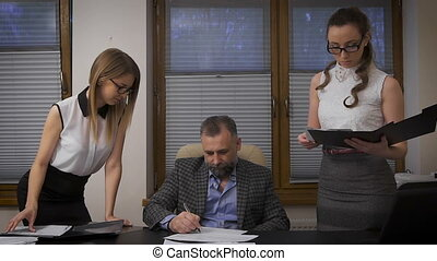 Two women assistants to apply for signature to his boss. A...
