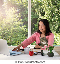 woman holding her family pet cat while working from home
