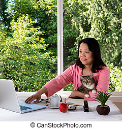 Mature woman holding her family pet cat while working from home