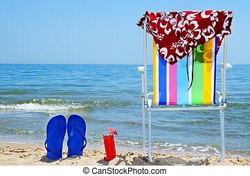summer on the beach - deckchair, swim suit, flip-flops and...