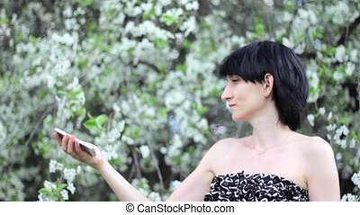 Pretty girl taking a selfie on flowering tree background -...