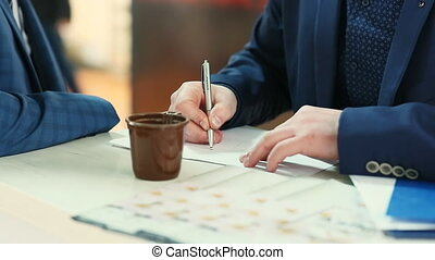 Businessman drawing business charts in copybook on desktop...