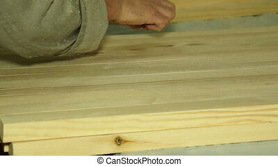 Marking of wooden pieces. - Worker marks wooden piece with a...